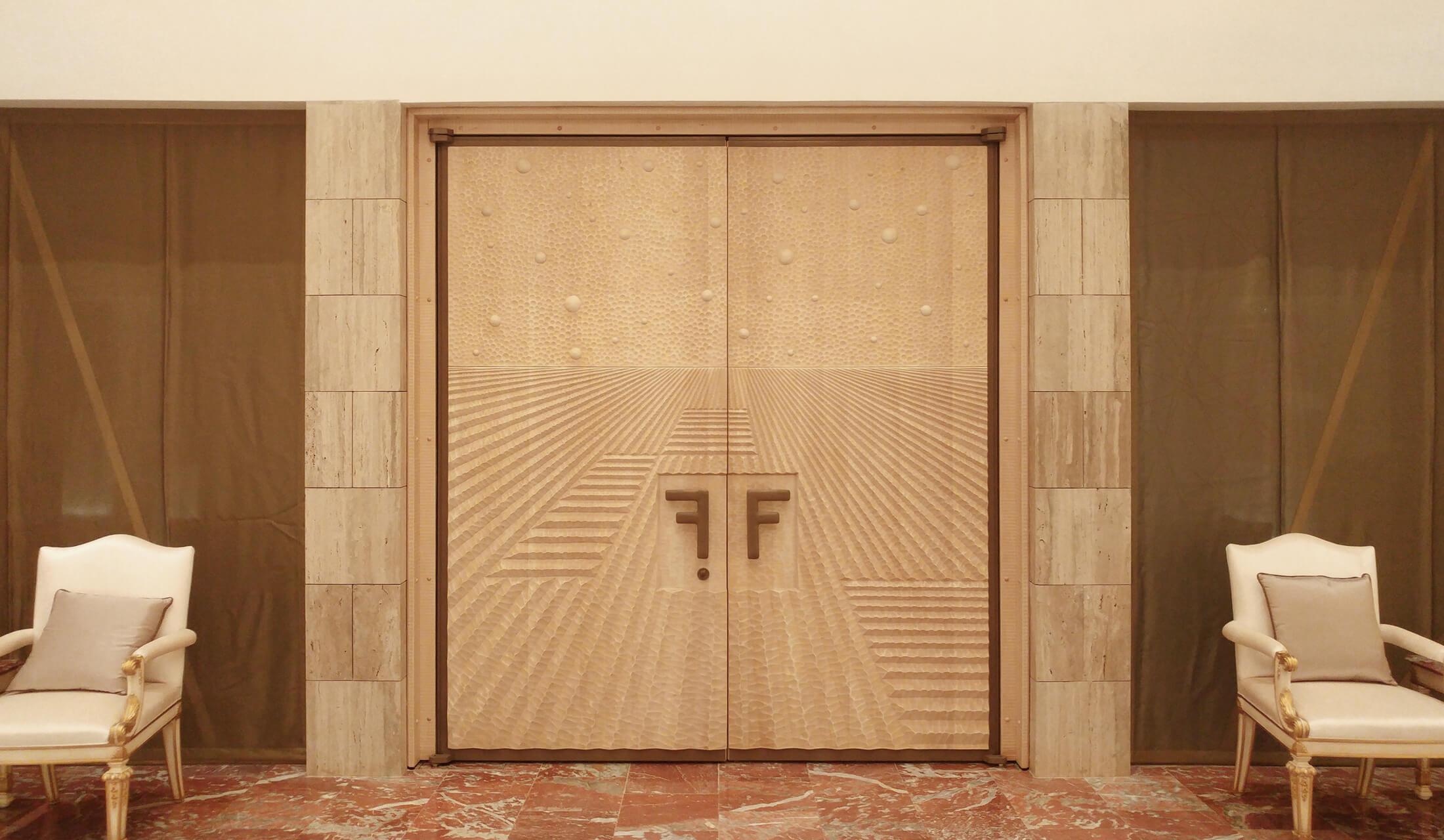 Grande porta a due battenti realizzata su progetto. Facciata esterna rivestita in bronzo, facciata interna in tiglio.
